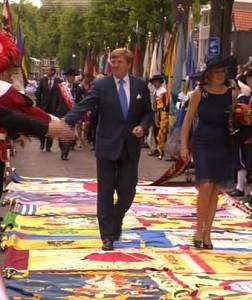 Koning Willem-Alexander en koningin Máxima lopen in Oisterwijk over de vaandels van Brabantse gilden.
